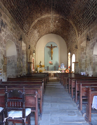 Inside the Mision de San Jose de Comondu. Arched ceiling, wooden benches.