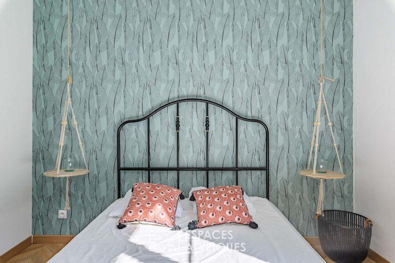 Dormitorio con papel pintado verde y mesita colgantes.