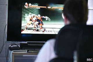 TV screen shows two players, one up against the wall being attacked in a video game.