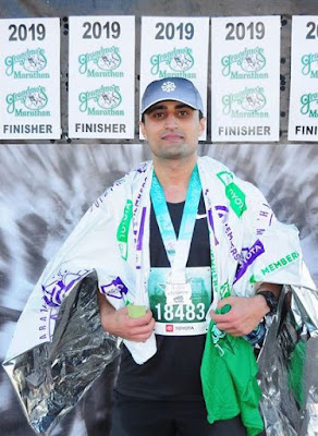 Babak Jahromi standing at the finish of the 2019 Grandma's Half Marathon