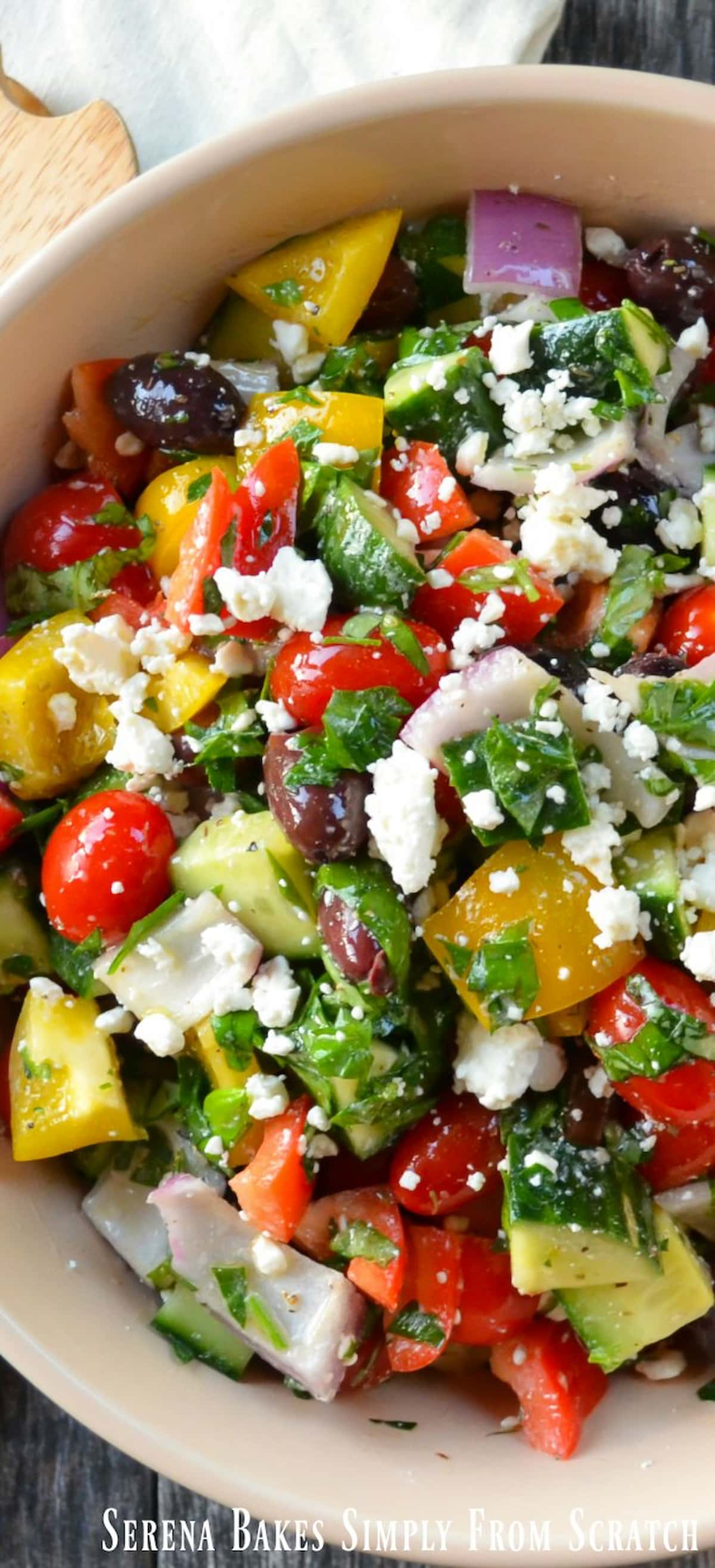 A down shot of Greek Salad in a cream colored bowl with cherry tomatoes, diced red bell pepper, diced yellow bell pepper, diced red onion, and feta cheese sprinkled over the top.