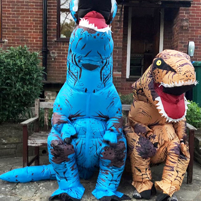 Two people in inflatable T-Rex dinosaur costumes sitting on bench