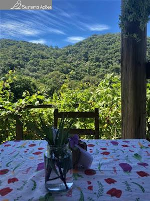 Mesa com arranjo de flor e montanhas ao fundo