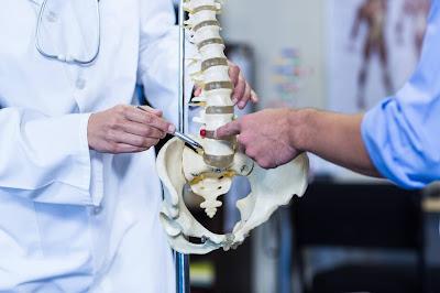 Doctor y paciente con columna vertebral