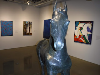 black sculpture of a horse visible in foreground, with various paintings visible in the background at the Sioux City Art Center