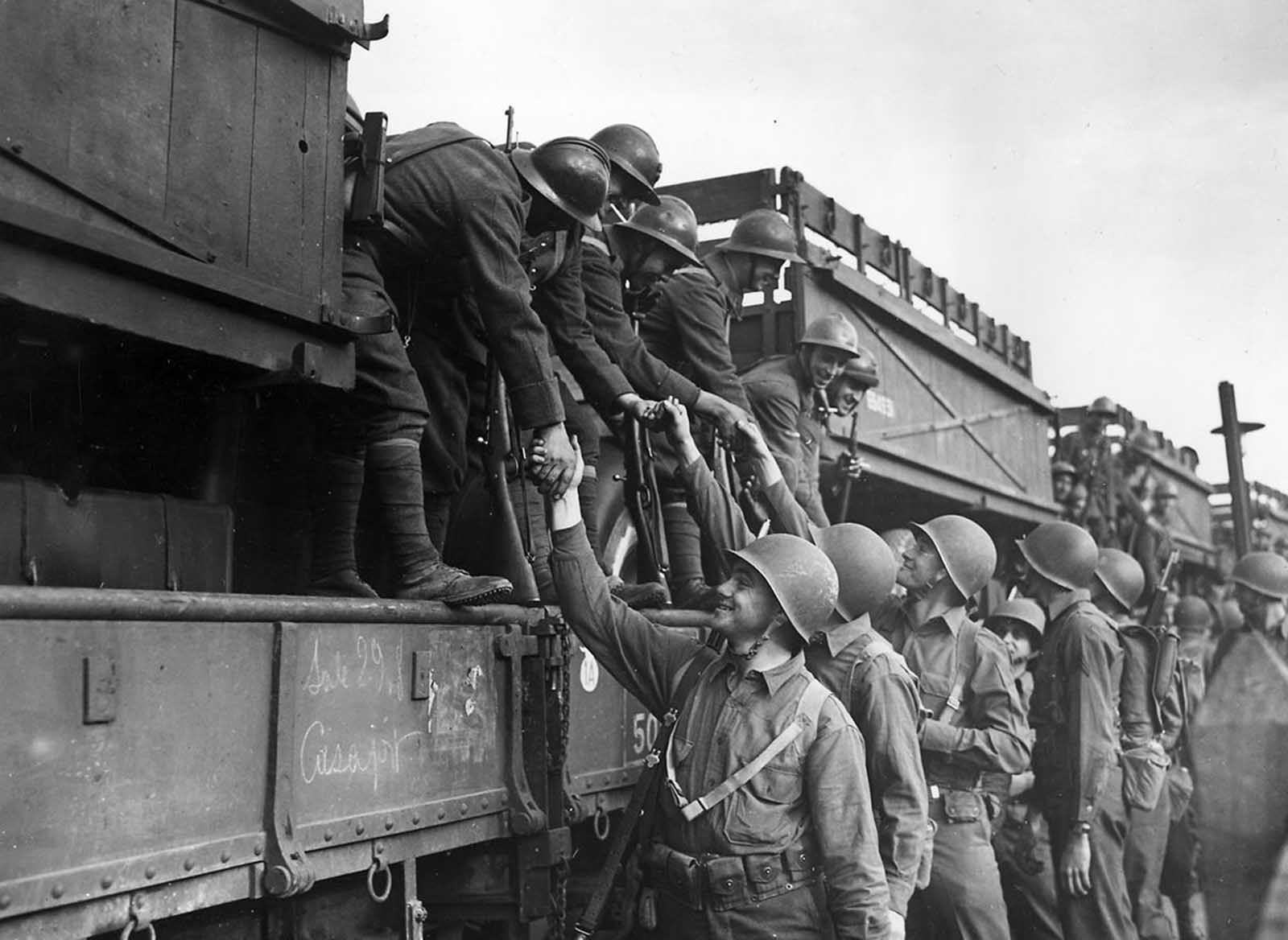 French troops on their way to the fighting lines in Tunisia shake hands with American soldiers at the rail station in Oran, Algeria, North Africa, on December 2, 1942.