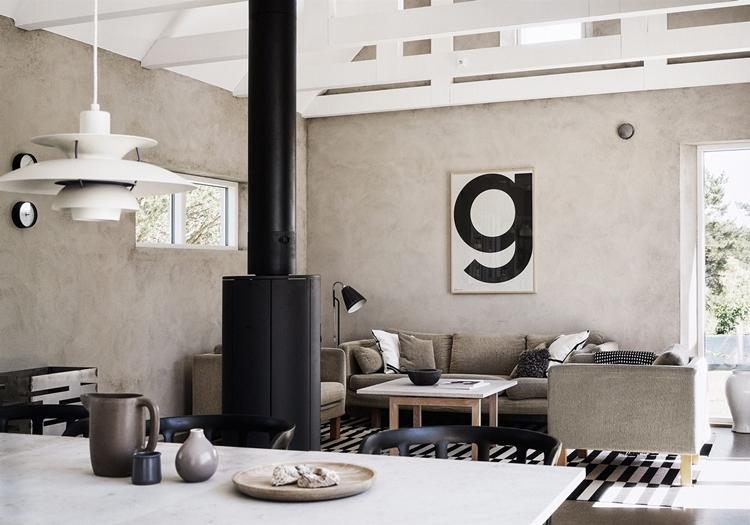salon-estilo-nordico-gris-lampara-sofa-gris-interiorismo-chimenea-mesa-sillas-pared-blanco-