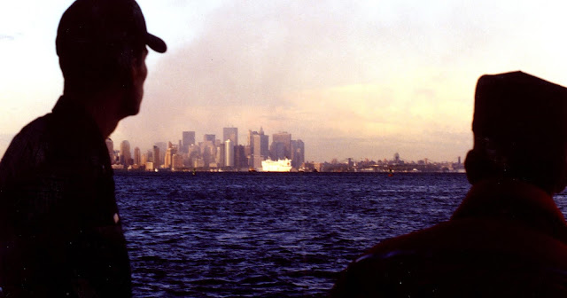 Coast guardsmen from Activities New York look on from Staten Island as the USNS Comfort arrives in New York harbor, with the World Trade Center complex burning in the background days after the September 11th attacks. (USCG photo by PAC Brandon Brewer)