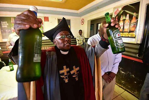 Bishop Tsietsi Makiti prays for drinks before they are served to congregants in his church. (Nairobi News)