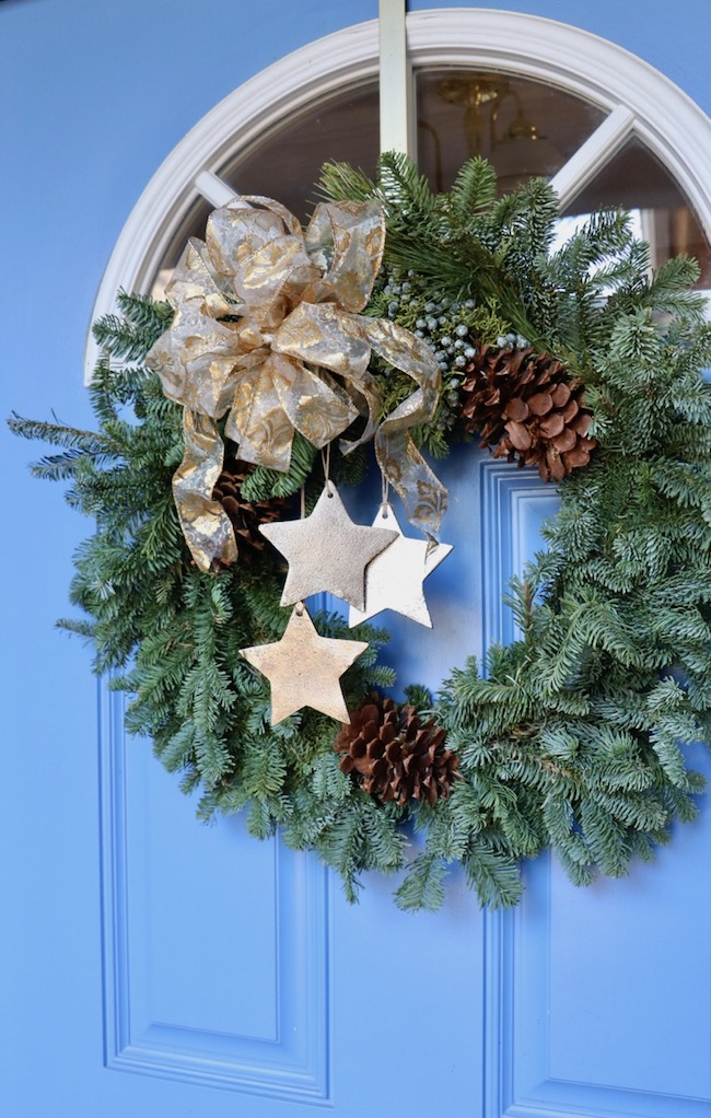 Tips for best ever Christmas wreath on blue front door with gold metal stars, fleur de lis ribbon box, and fresh greenery filled gaps