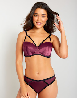 A bright pink bra with black edges and black thin straps with a matching v shaped panty that is bright pink with a black edge trim on a white background.
