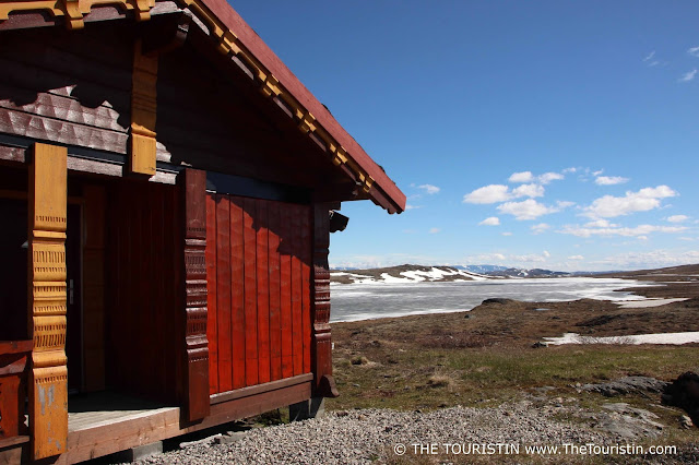 A red wooden cabin on the Hardangervidda Mountain Plateau in Norway with a partly frozen lake in the background