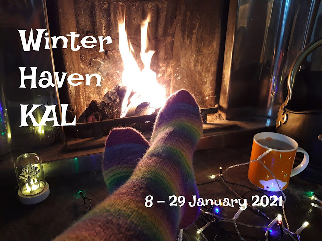 A fire is burning in an open fireplace with a pair of feet in multi-coloured socks stretched out in front of it.  There are fairy lights to the right, an orange mug of tea and a small Christmas decorative light on the hearth to the left