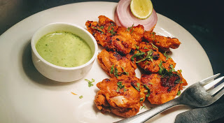 Chicken tikka on a serving plate with green chutney