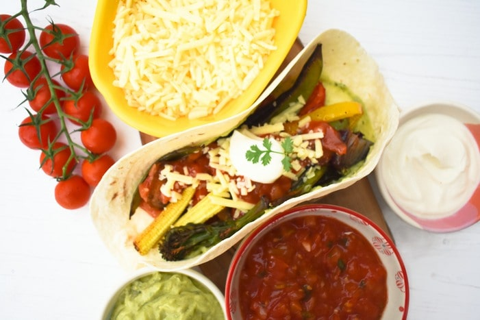 Sheet Pan Vegetable Fajita on a wooden board with bowls of grated cheddar, salsa and guacamole