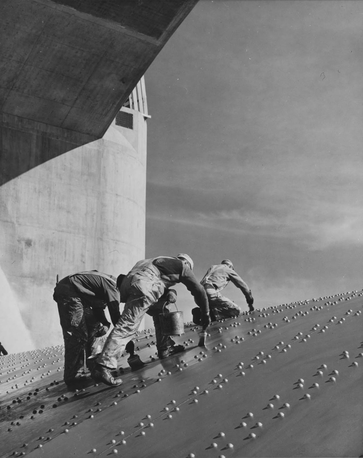 Workers apply a coat of paint to one of the dam's spillways. 1936.