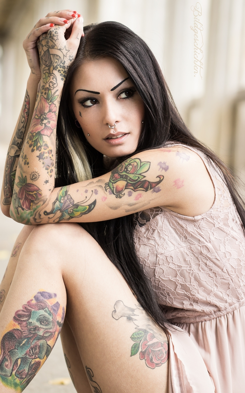 Espectacular mujer latina, sentada, vemos sus tatuajes en colores de estilo new school