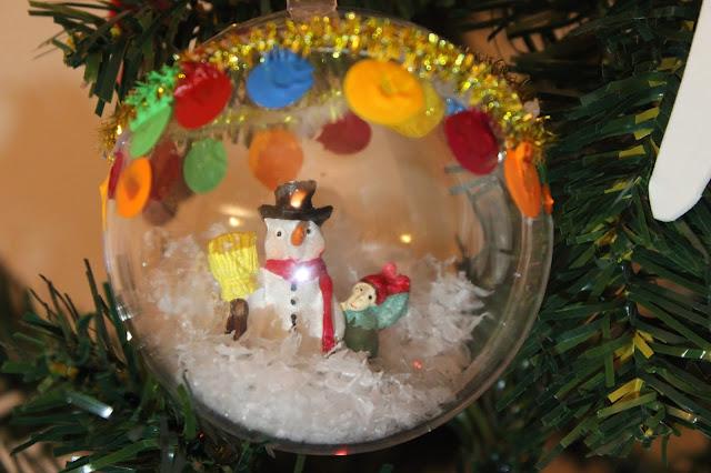 Bola de Natal, transparente, com um boneco de neve e neve artificial dentro, feita à mão
