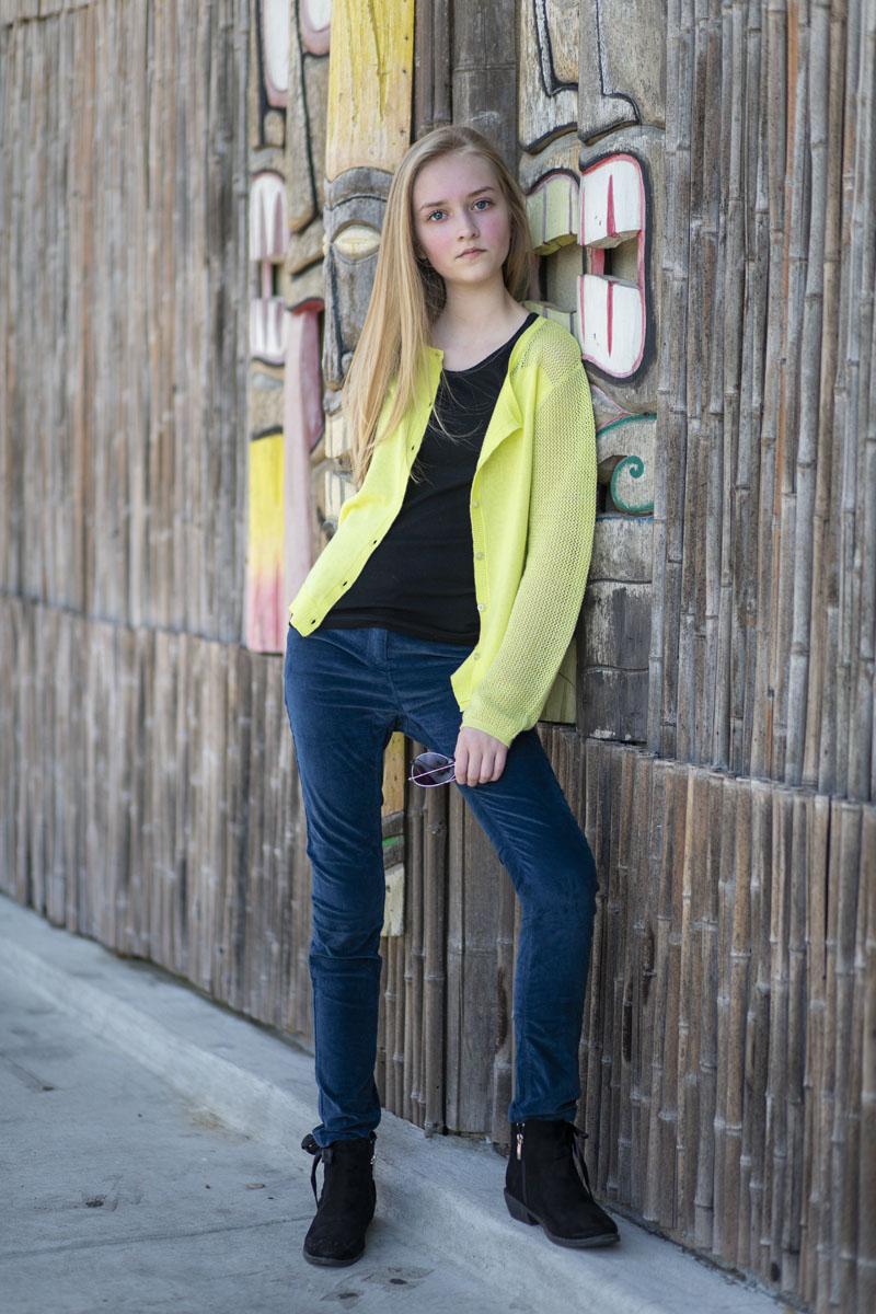 tween model wearing Graffiti Gloss velvet pants and neon cardigan