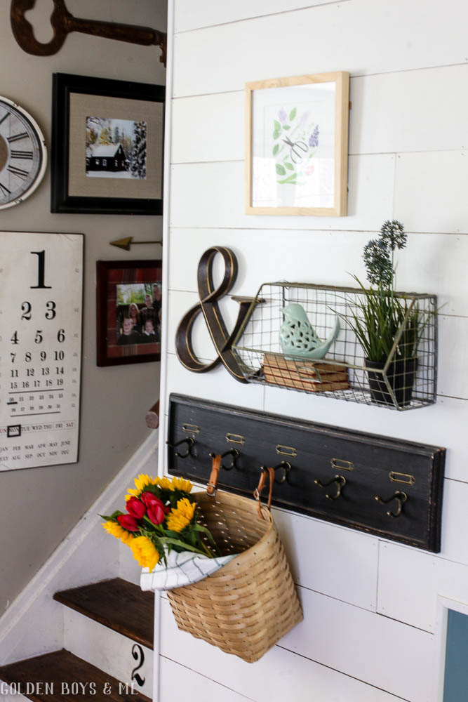 Gallery wall with wire basket and hooks in spring entry