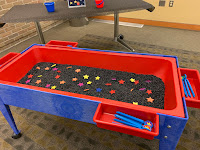 discovery bin filled with dried black beans and colorful foam star shapes