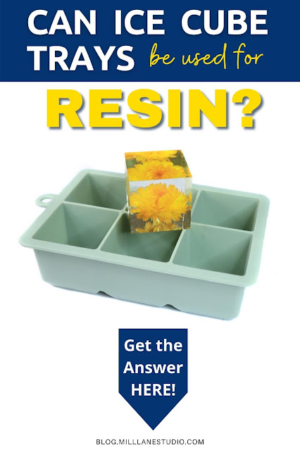 Yellow straw daisy encased in a clear resin cube, sitting on top of a sage-coloured ice cube tray with 6 cavities