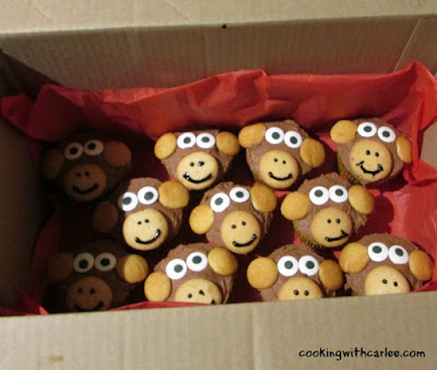 box full of cupcakes decorated like monkeys