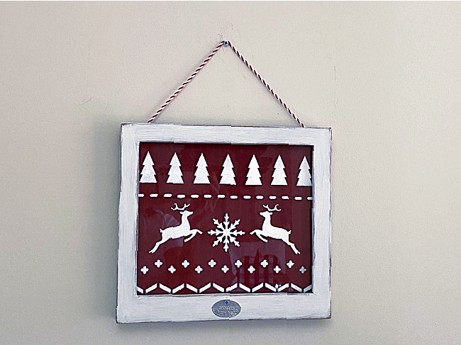 Stenciled sweater pattern sign in a white frame