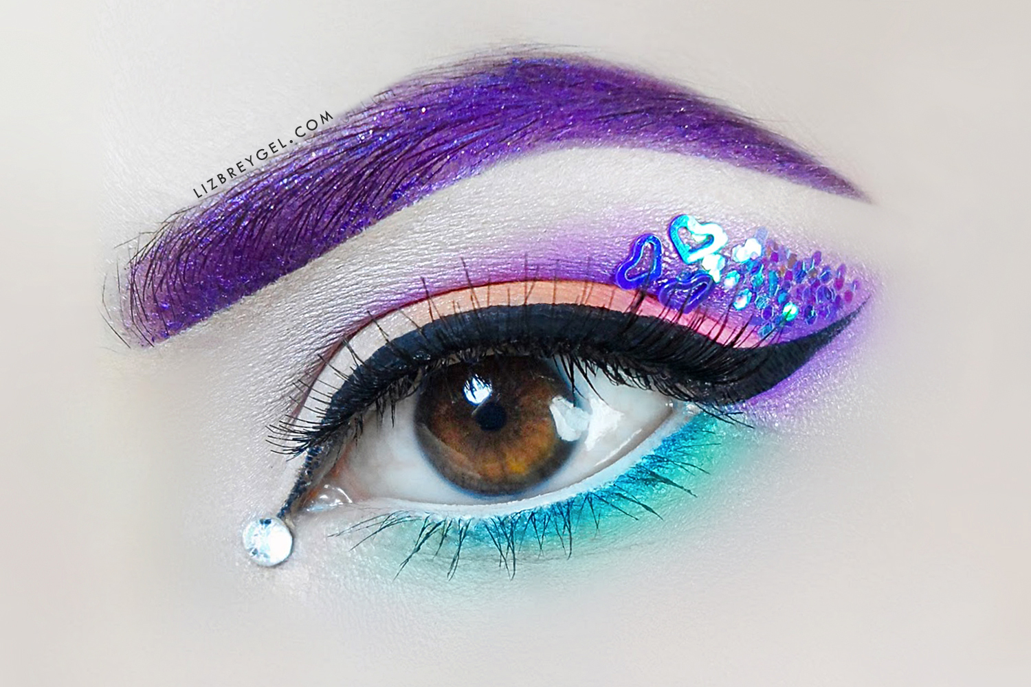 a close up of eye with bright, unicorn makeup
