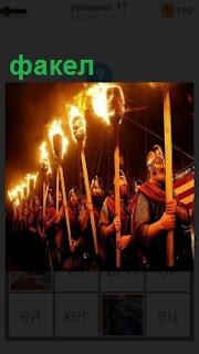 Несколько человек в ряд, друг за другом несут факела в темное время суток
