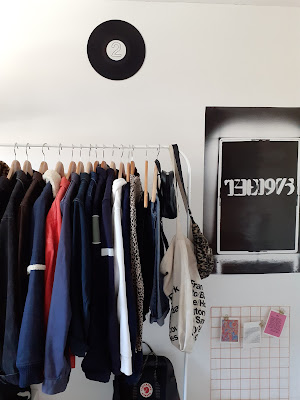 minimalistic room with clothing rail and poster, metal grid wall display, the 1975 poster, records on wall