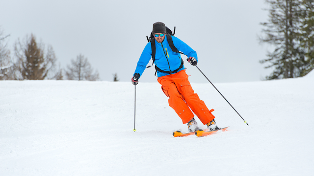 bundled up skiier using poles for balance