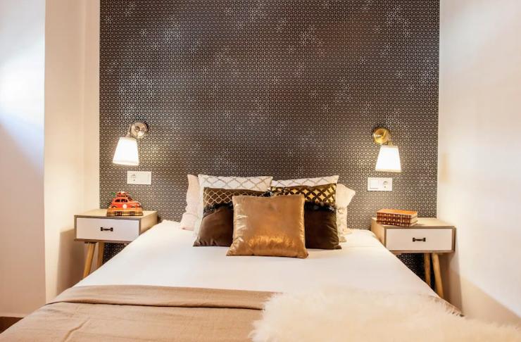 Cómo decorar una casa para alquilar: dormitorio con pared frontal con papel pintado.