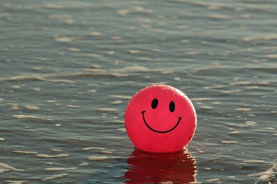 red laughing balloon on water