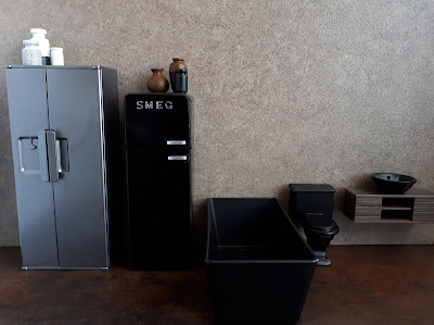 Two one-twelfth scale modern miniature fridges,a bath, a toilet and a basin displayed in a line. On top of the fridges are a collection of jars and vases.