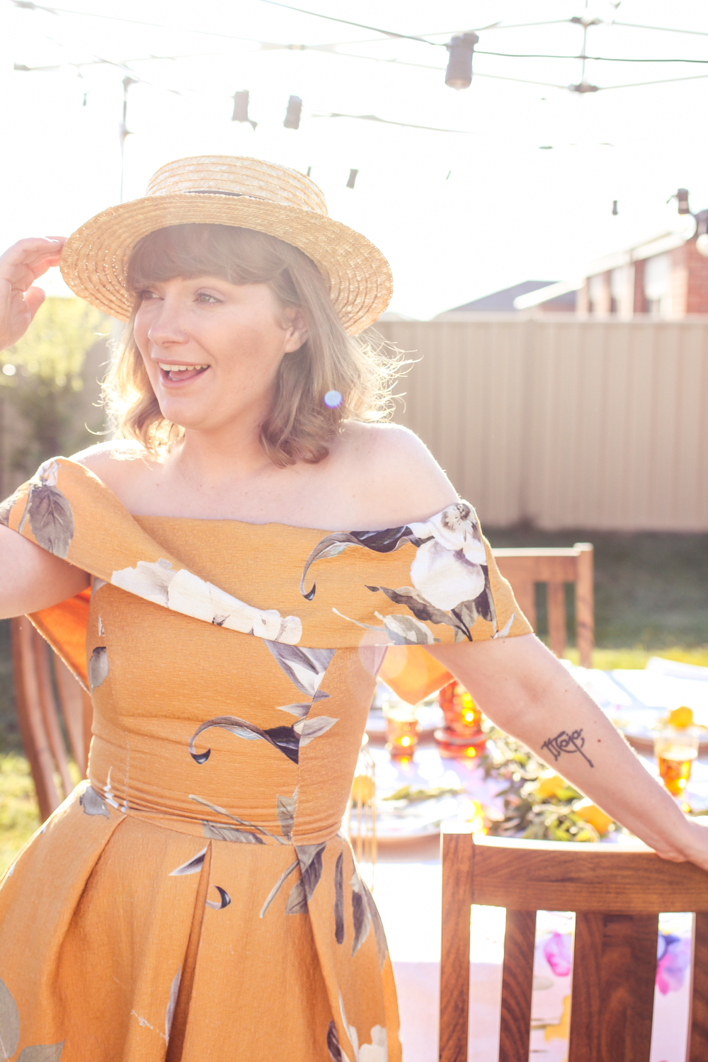 Liana of @findingfemme wears yellow floral asos dress at backyard dinner party.