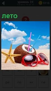 На солнечном берегу летом лежит кокос с трубочками внутри, солнцезащитные очки и морская засушенная звезда