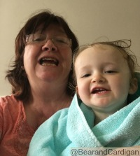 lady and toddler saying cheese. toddler wrapped in towel