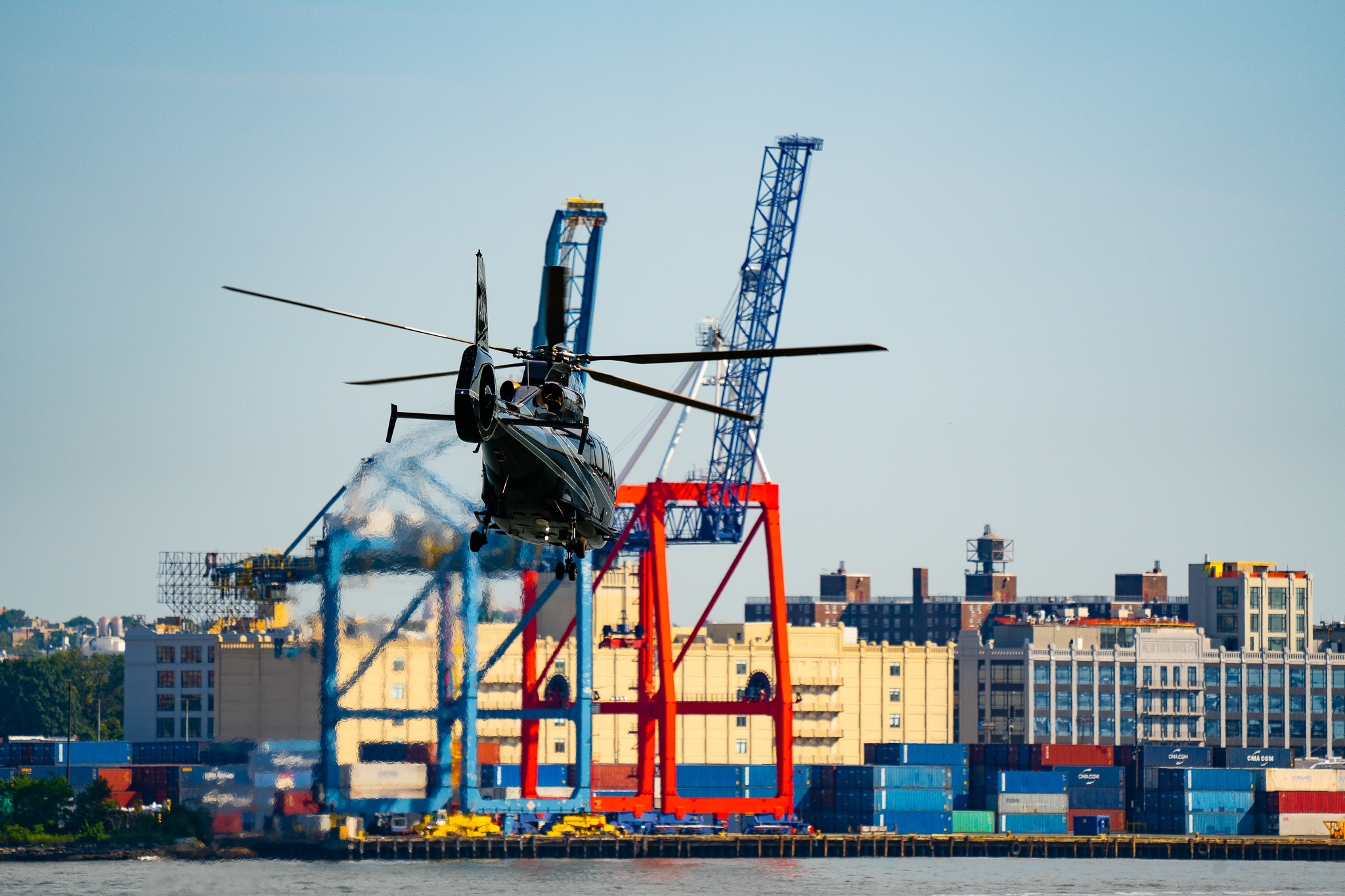 a photo of a black helicopter taking off over new york east river