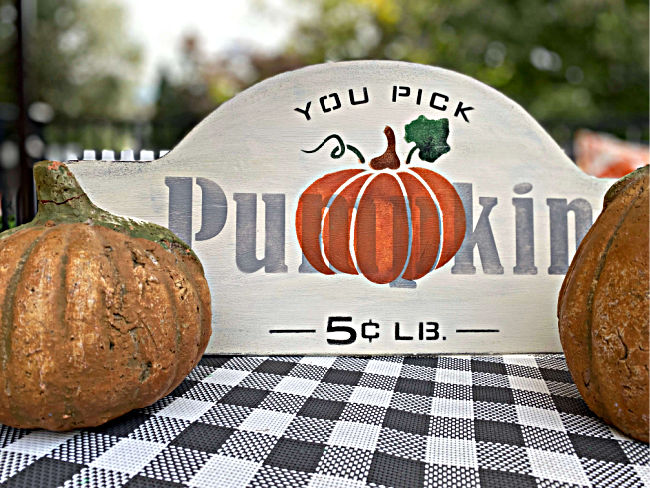 metal pumpkin sign surrounded by pumpkins