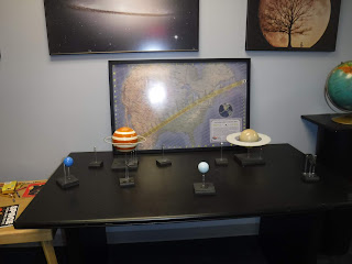 a model of the solar system sits atop a black desk at the Fred G. Dale Planetarium in Wayne, Nebraska