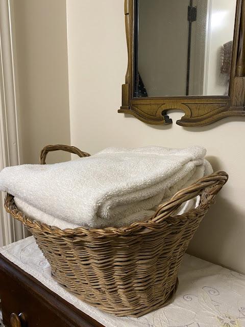 vintage wicker laundry basket holds towels
