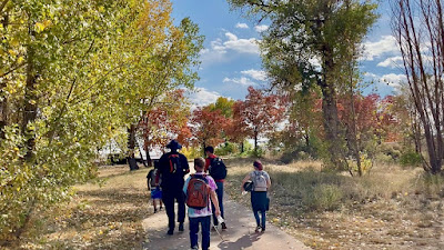 5 CCB students walking on a trail through trees whose leaves have changed from green to yellow and red