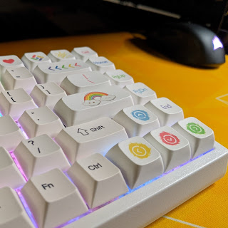 The right side of a white ten-keyless mechanical keyboard on a yellow desk mat, with a black mouse in the background. Most of the key caps are standard white with black blocky font, but the function keys and most of the right panel have been replaced by taller keys with either coloured text or icons. The enter key has a rainbow with little clouds at either end, the arrow keys are each a different colour and look like paint splatters with white arrows, the back space has 5 arrows pointing left (backwards), each a different colour of the rainbow.