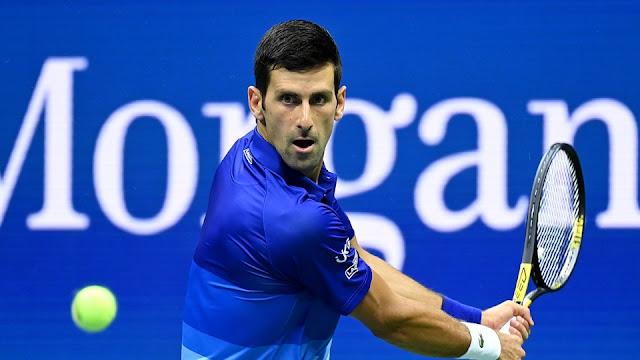 Novak Djokovic prepara um golpe de backhand, olhando fixamente a bola e segurando firmemente sua raquete