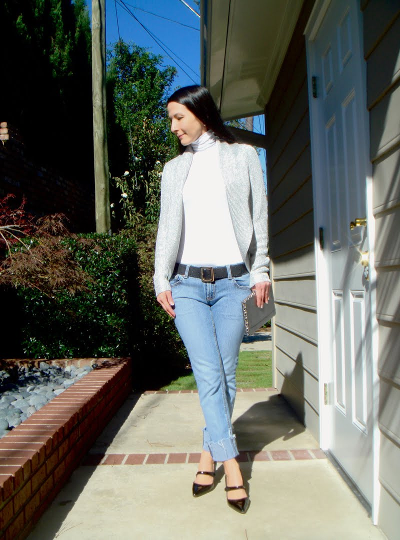 Wearing cuffed jeans, a white turtleneck, a silver metallic circle cardigan with a black belt with gold buckle. Carrying a silver rectangular clutch with chain detail around it. And black mary janes.