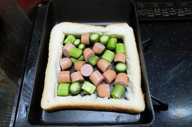 火にかける前にアスパラガスとウィンナーの1回分の量を量りたいので、食パンのミミがついている方を置いて、その中にアスパラとウィンナーをすき間なく並べ入れて使う分を量ります。 炒めると少し縮むので、「ちょっと多いかな」程度で大丈夫です。