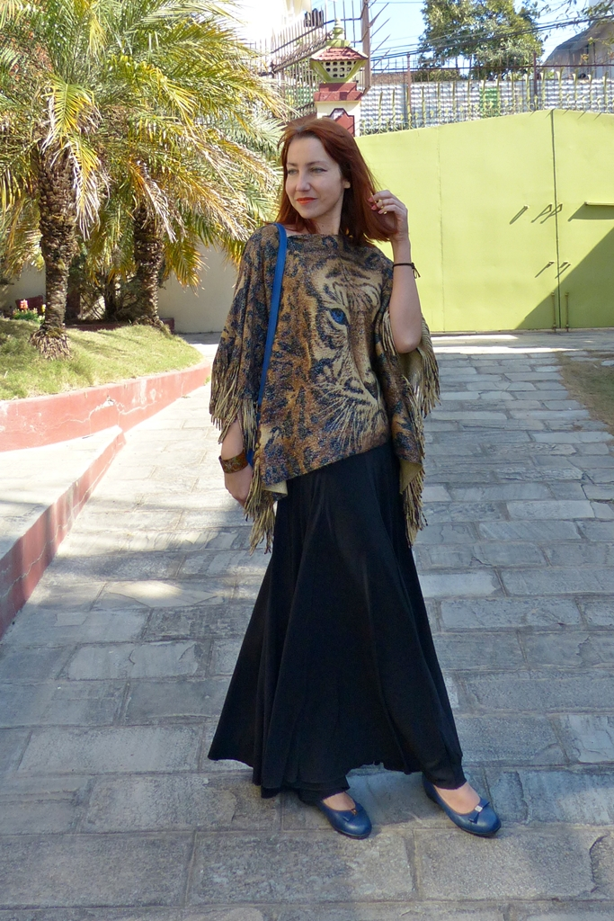 Fringed poncho worn with maxi skirt