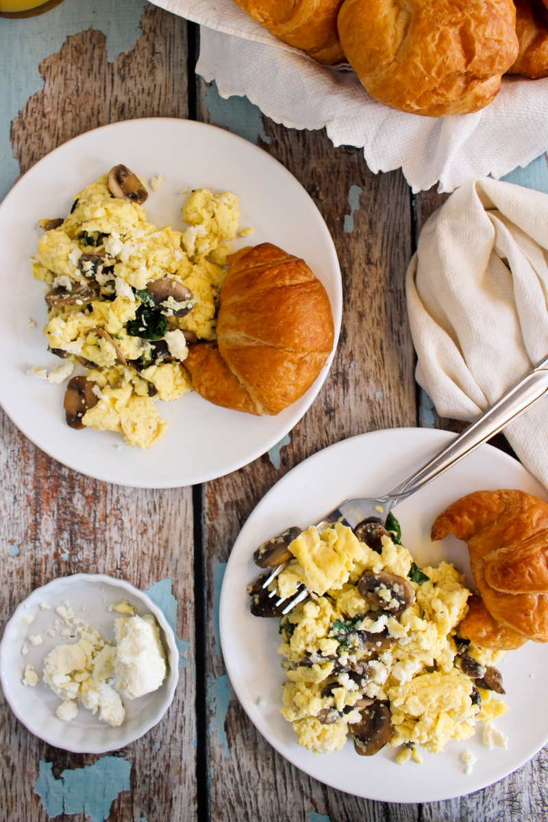 Top view of two white plates with mushroom scrambled eggs and a croissant next to a basket of croissants.