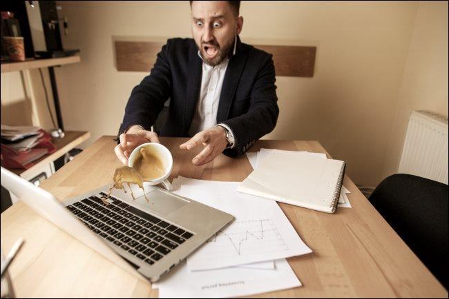 رجل يسكب القهوة على جهاز كمبيوتر محمول.